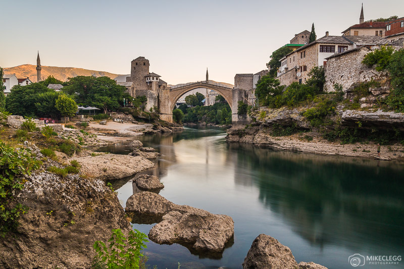 Mostar along the Neretva river with rocks in the foreground