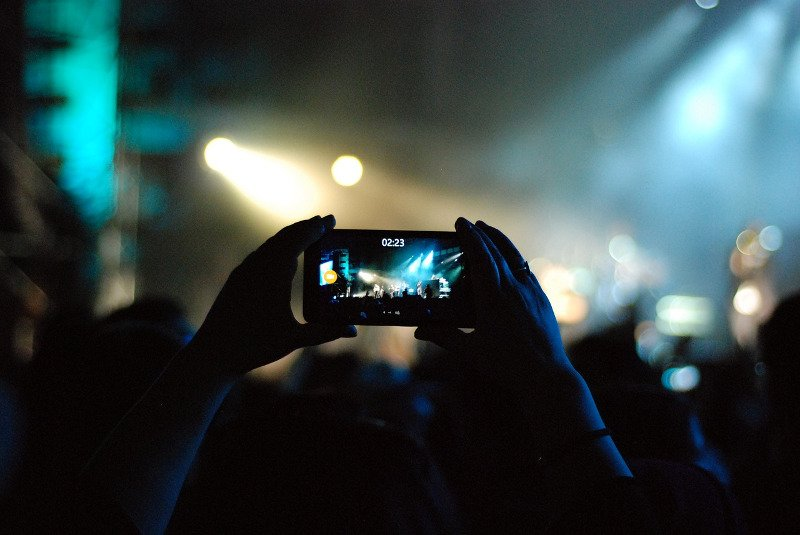 A person recording on a phone at a festival - CC0 (Pixabay)