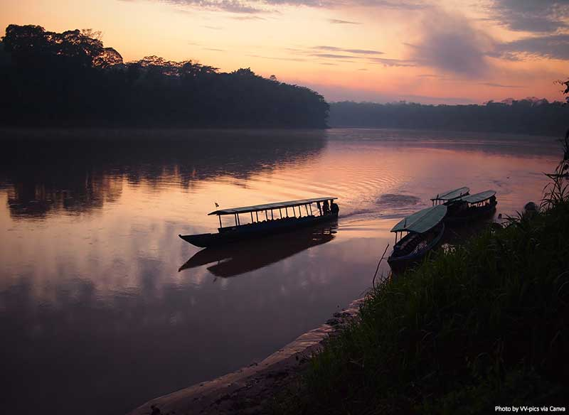 Amazon rainforest at sunrise with a boat