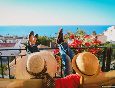 Couple relaxing on a balcony with scenic views